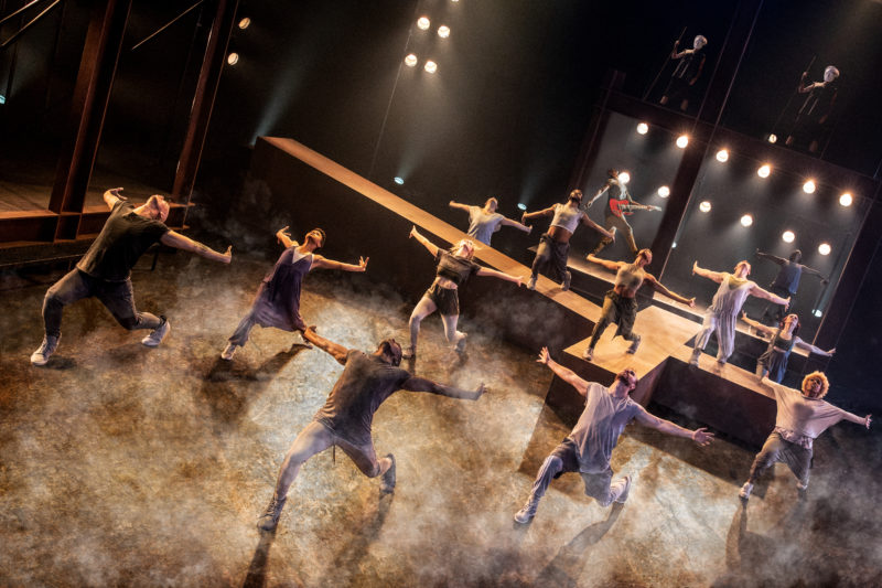 The chorus poses with arms outstretched on stage and on top of a giant wooden cross on stage.